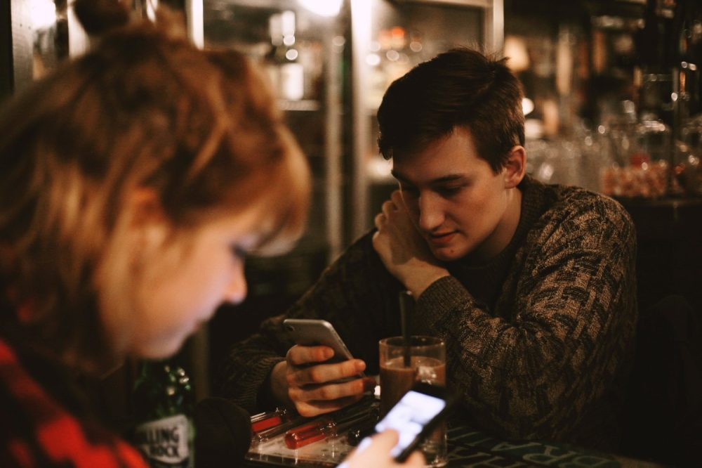 Friends texting on smartphones
