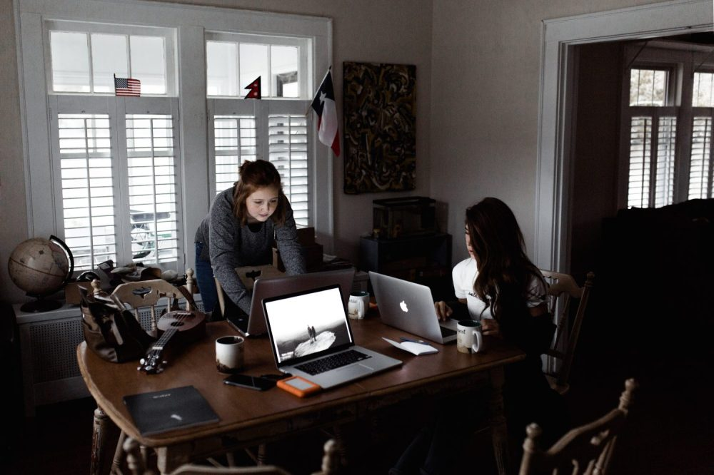 Two women working together on laptops